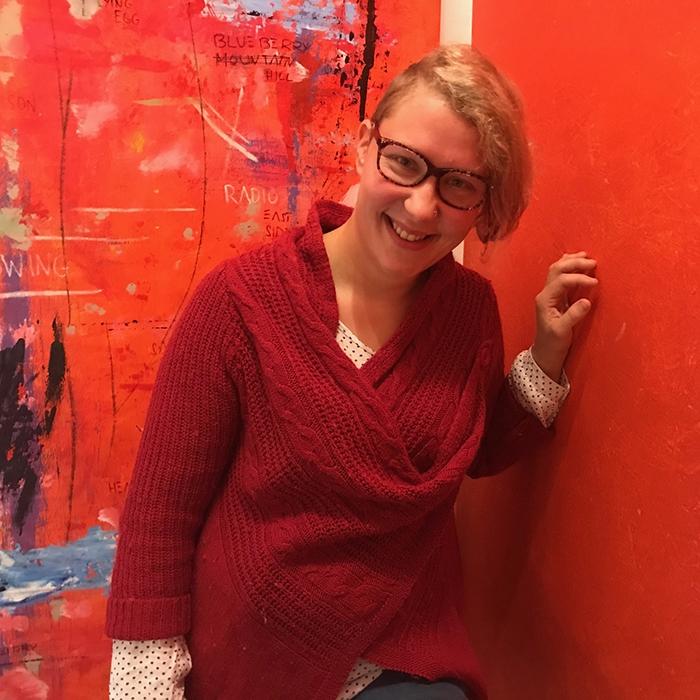 Musiikinopettaja Petra Lisitsin-Mantere nojaa punaista seinää vasten.