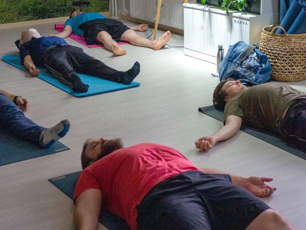 Viisi miestä joogaa. He rentoutuvat lattialla.