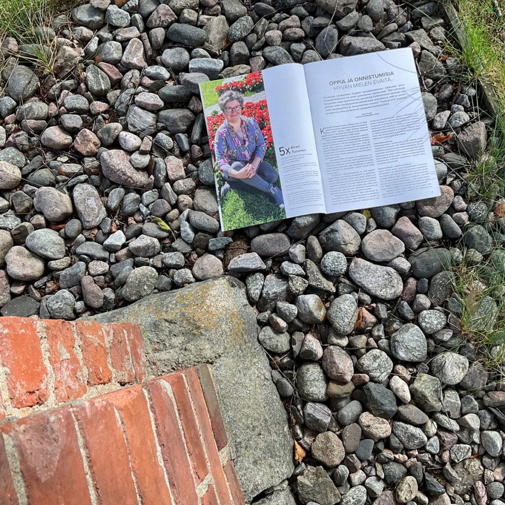 Yhdessä-lehden aukeama kuvattuna kivien päällä.